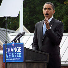 "Obama gestures from the podium while campaigning. The front of the podium has a sign that reads ""Change We Need"" with WWW. BARACKOBAMA. COM below and his campaign logo above."